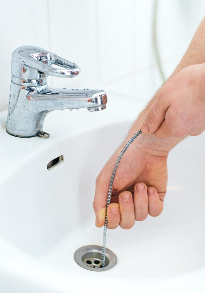 person snaking the drain of faucet