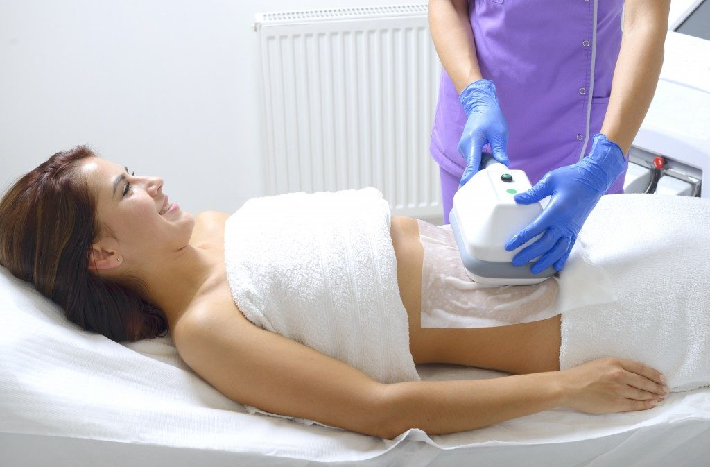 Pretty young woman getting cryolipolyse treatment