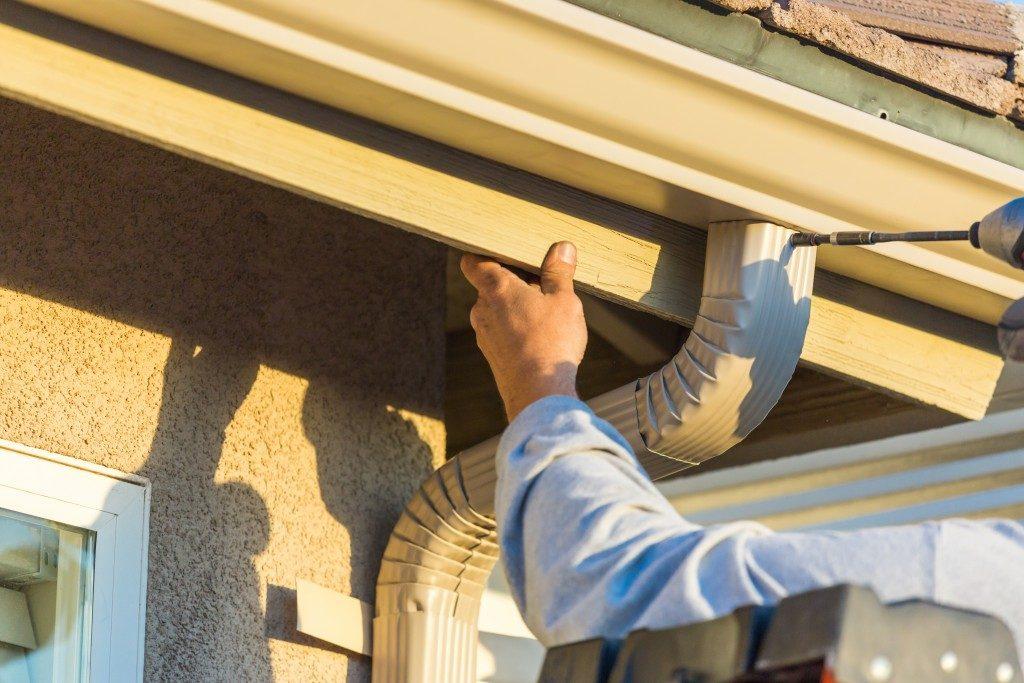 Worker installing an aluminum roof gutter