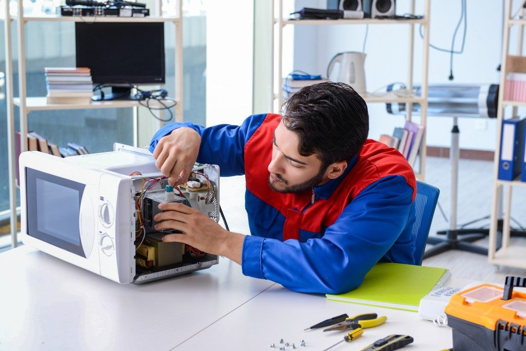 man fixing microwave