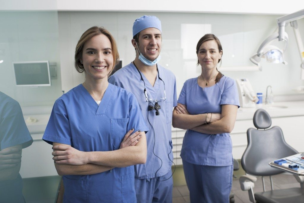 dentist and assistants standing in the dental office