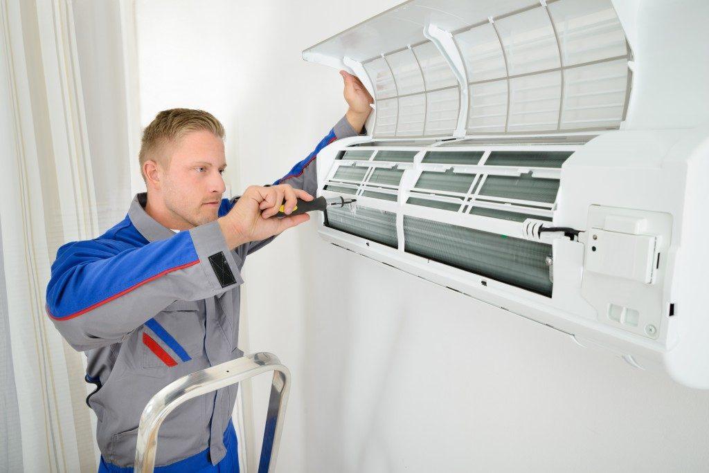 Electrician Repairing Air Conditioner