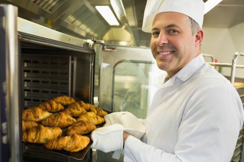 man placing bread on food warmer cabinet