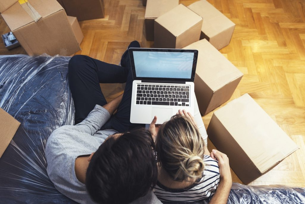 Couple using laptop while moving