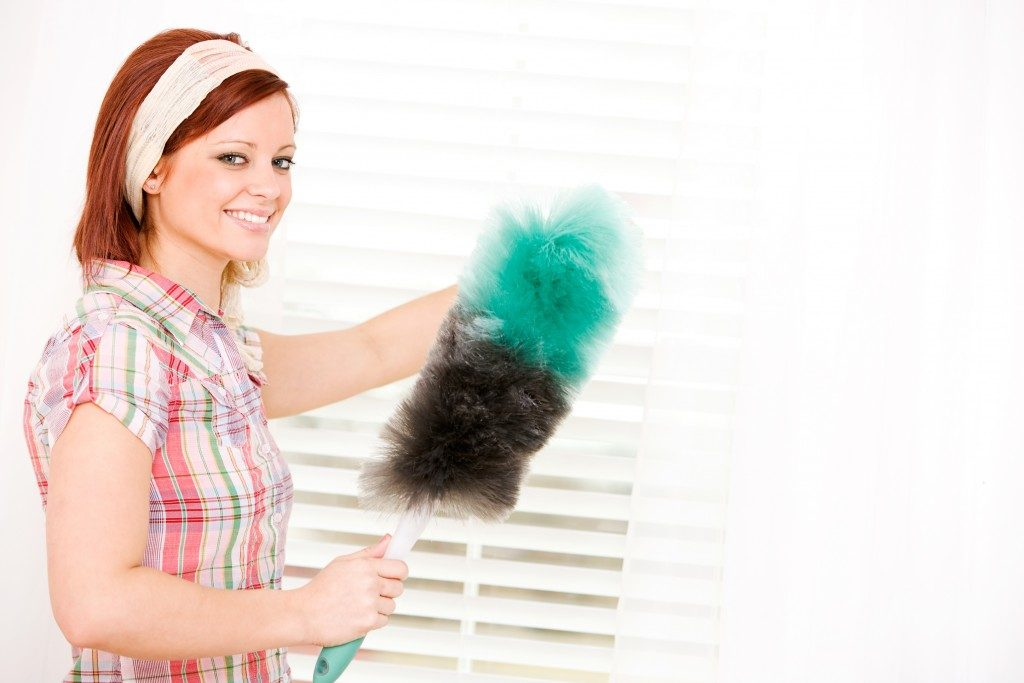 Woman dusting the blinds
