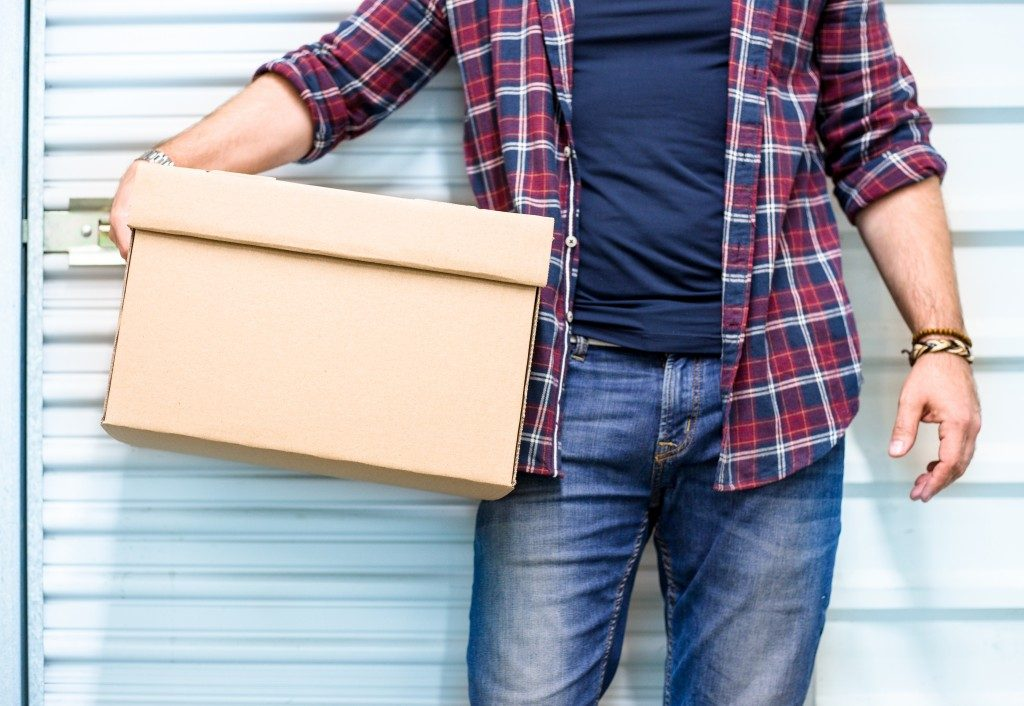 man standing outside a garage holding a box