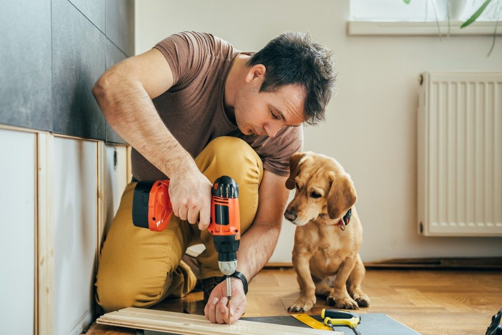 man using driller with his dog