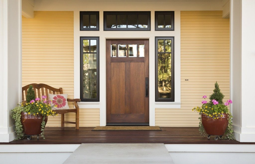 wood front door with plants and wooden chair on the entry way
