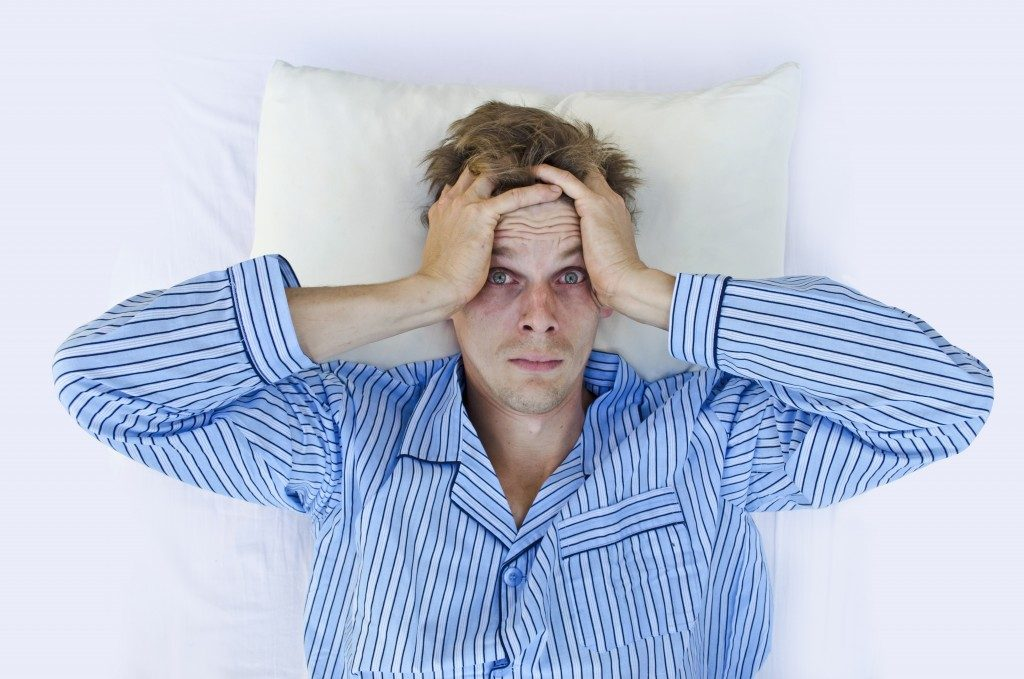 Man laying in bed with no sleep
