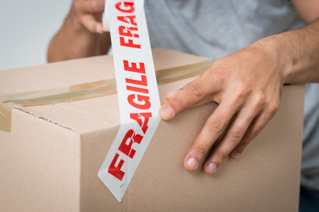 man putting fragile sticker on top of the box