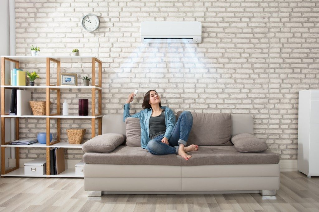 woman sitting in a sofa, enjoying the cool temperature from aircon