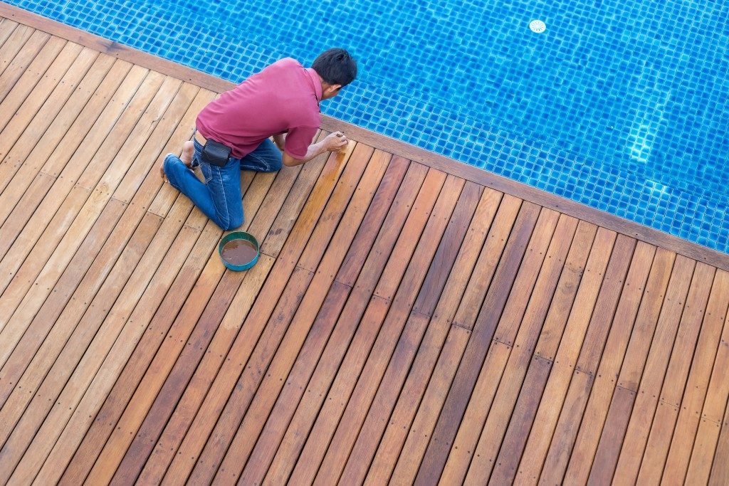 Man reapplying varnish to the wooden deck