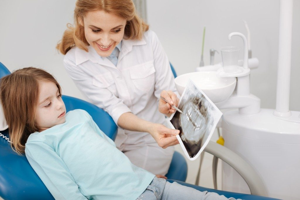 dentist showing a dental xray to a child