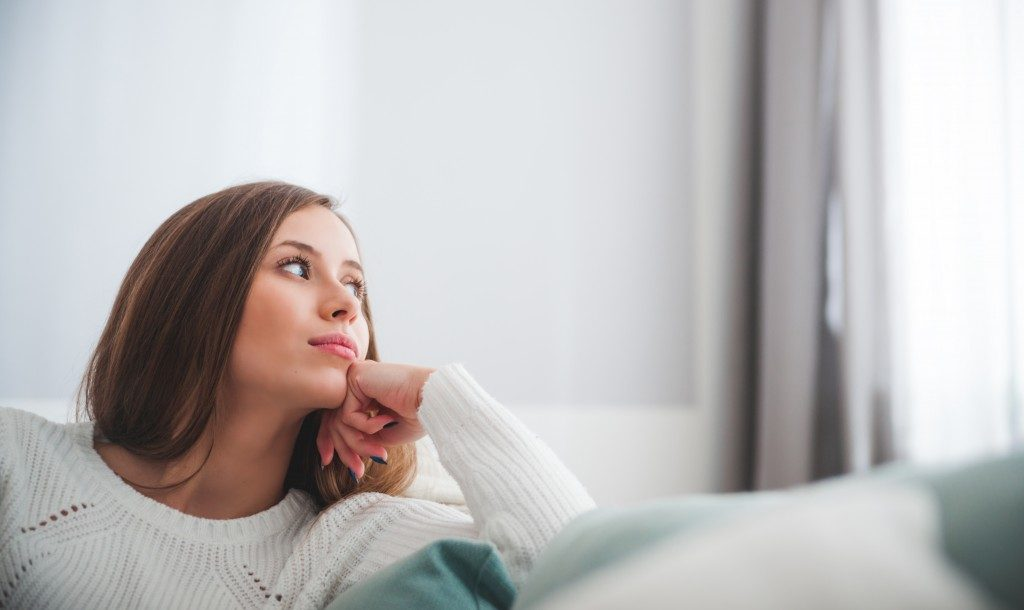 woman looking outside of the window from the couch
