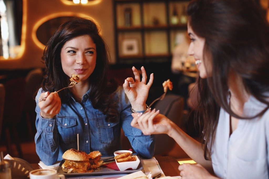 women eating burgers