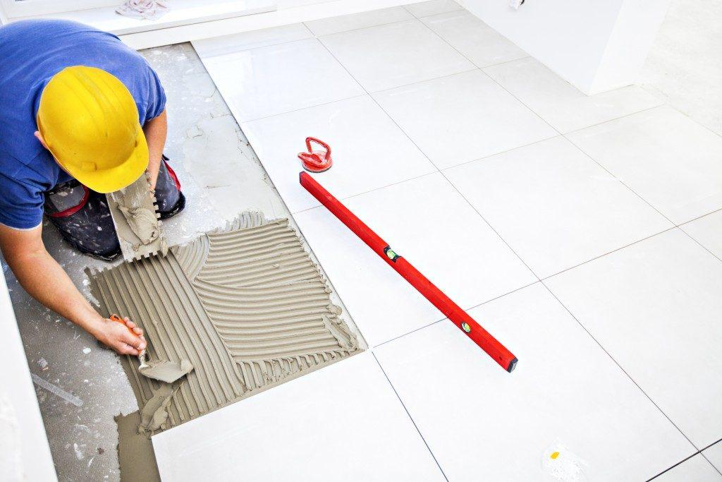 construction worker installing bathroom tiles