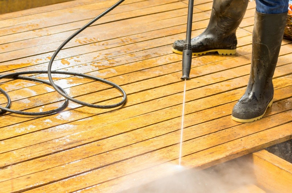 Man wearing rubber boots using high water pressure cleaner on wooden deck surface.