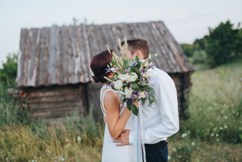 Couple kissing after wedding with wooden house in the background