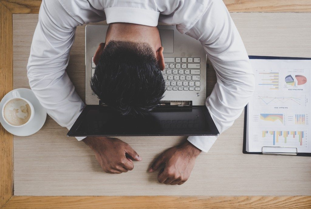 Man overworked experiencing fatigue in his office desk