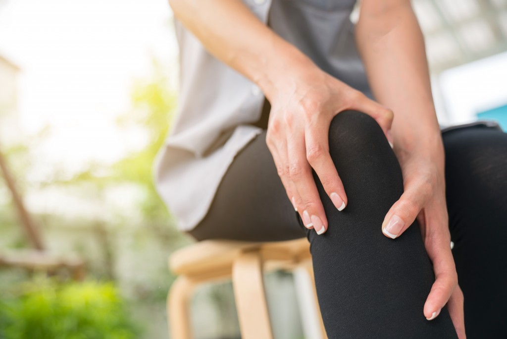 woman holding her leg because of pain