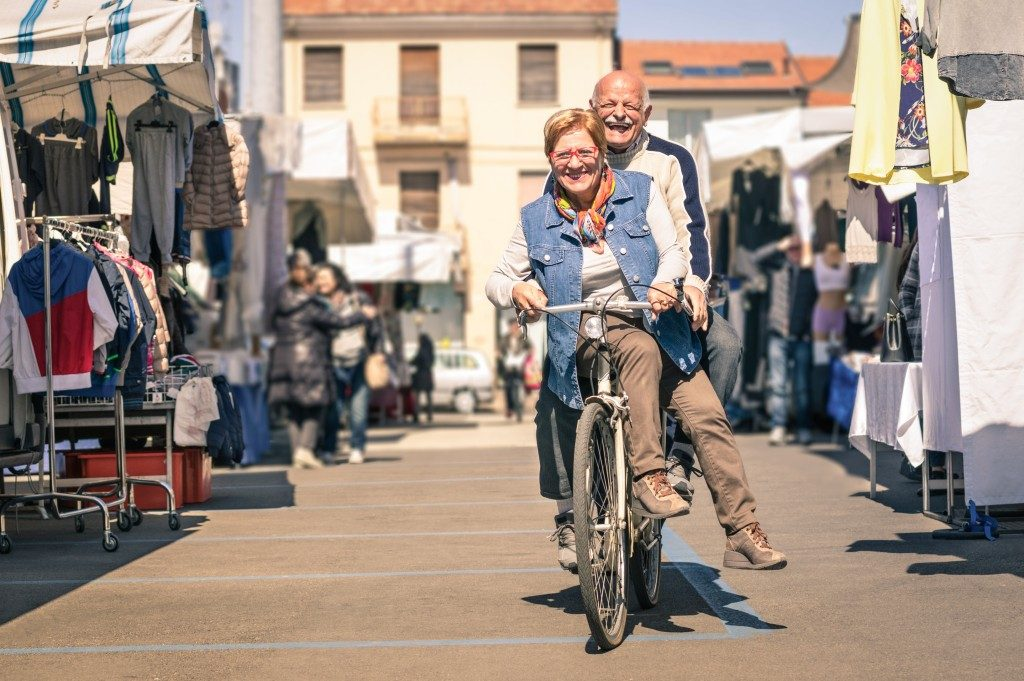 Happy senior couple having fun with bicycle