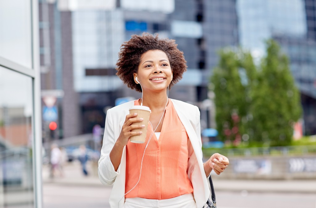 woman on her way to work while having a coffee