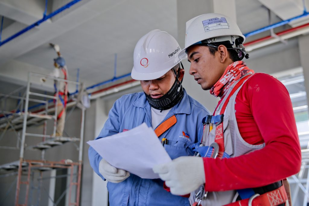Two construction workers reading a document