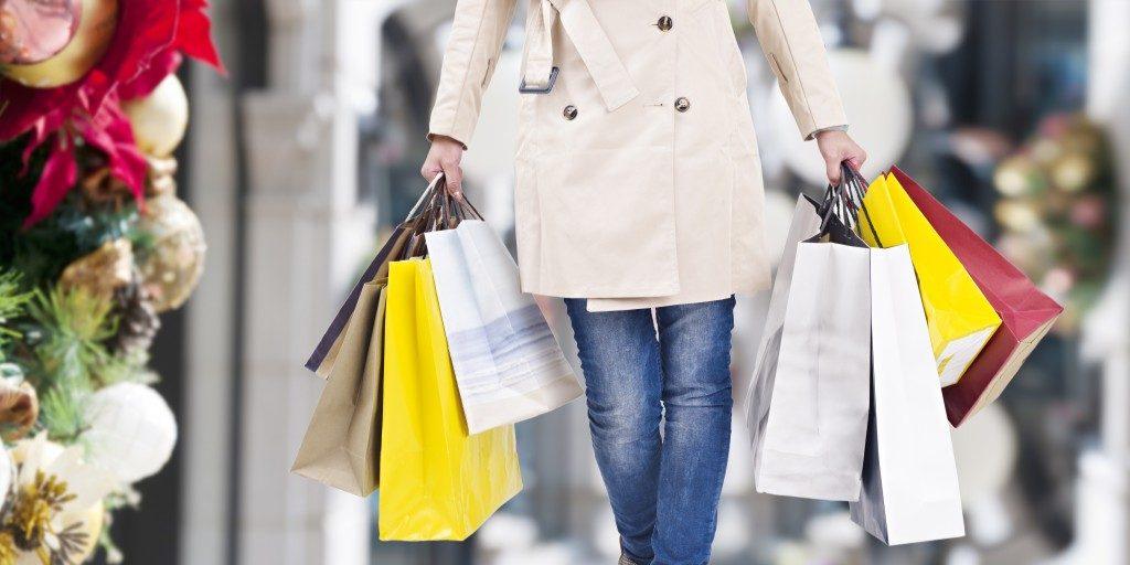 woman walking, hands full of shopping bags