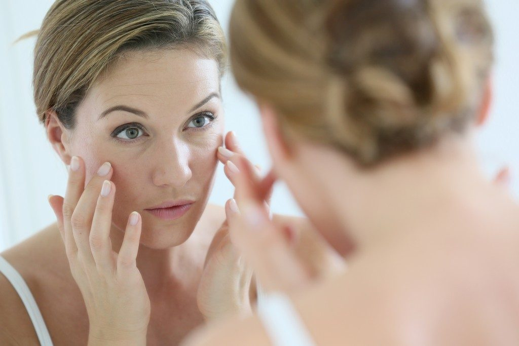 woman checking the wrinkles on her face