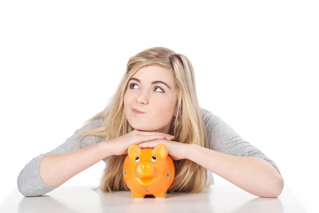 Image of a cute teenage girl posing with piggy bank.