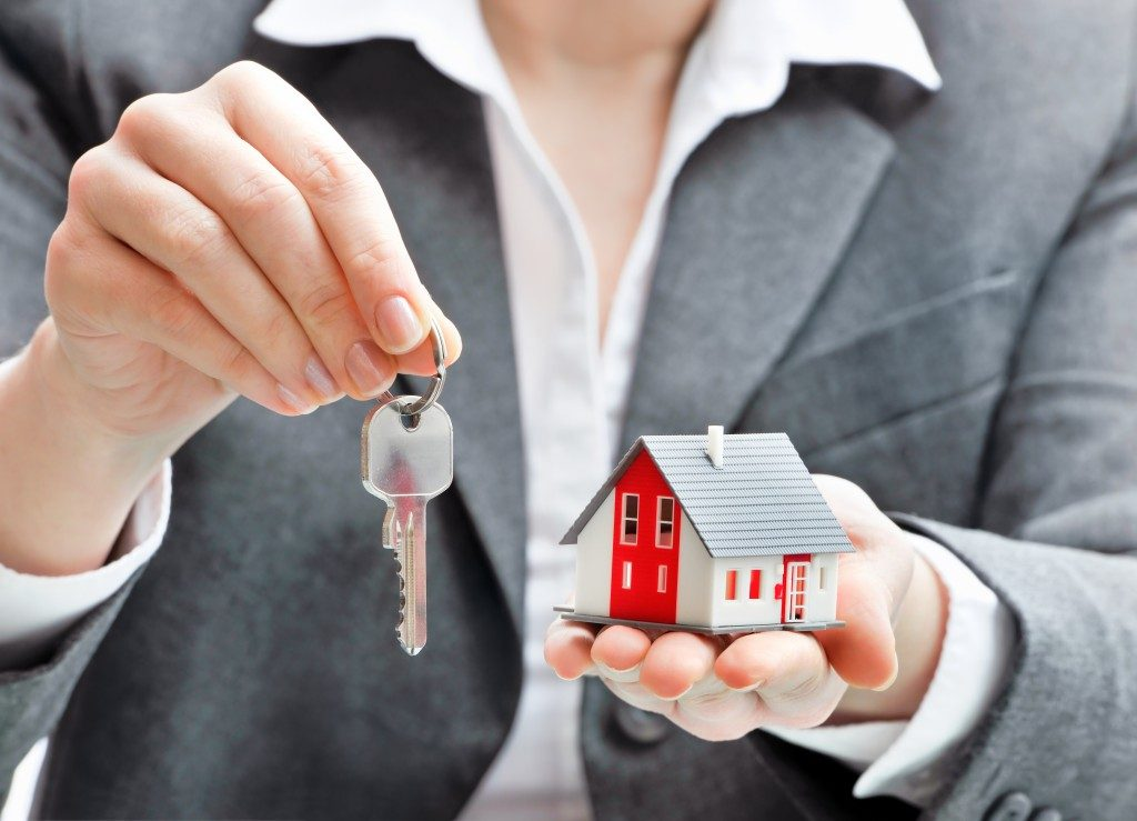 woman holding a house model and keys