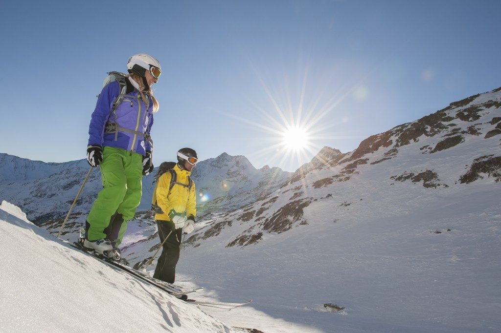 two skiiers watch the departure