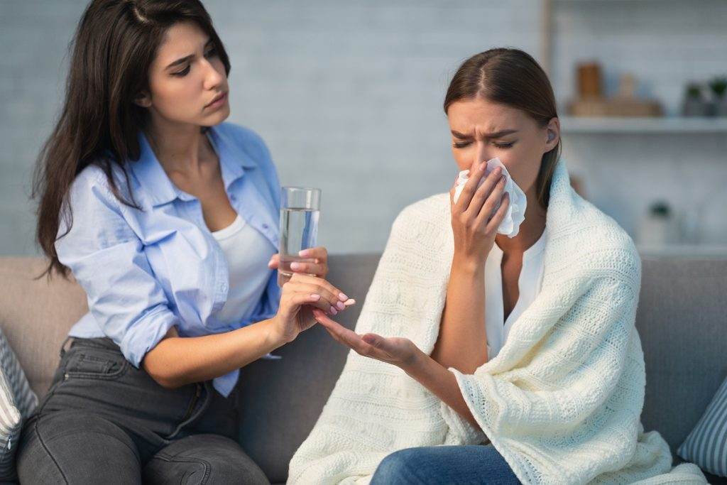 Girl Giving Pills To Sick Roommate Sitting On Couch Indoor