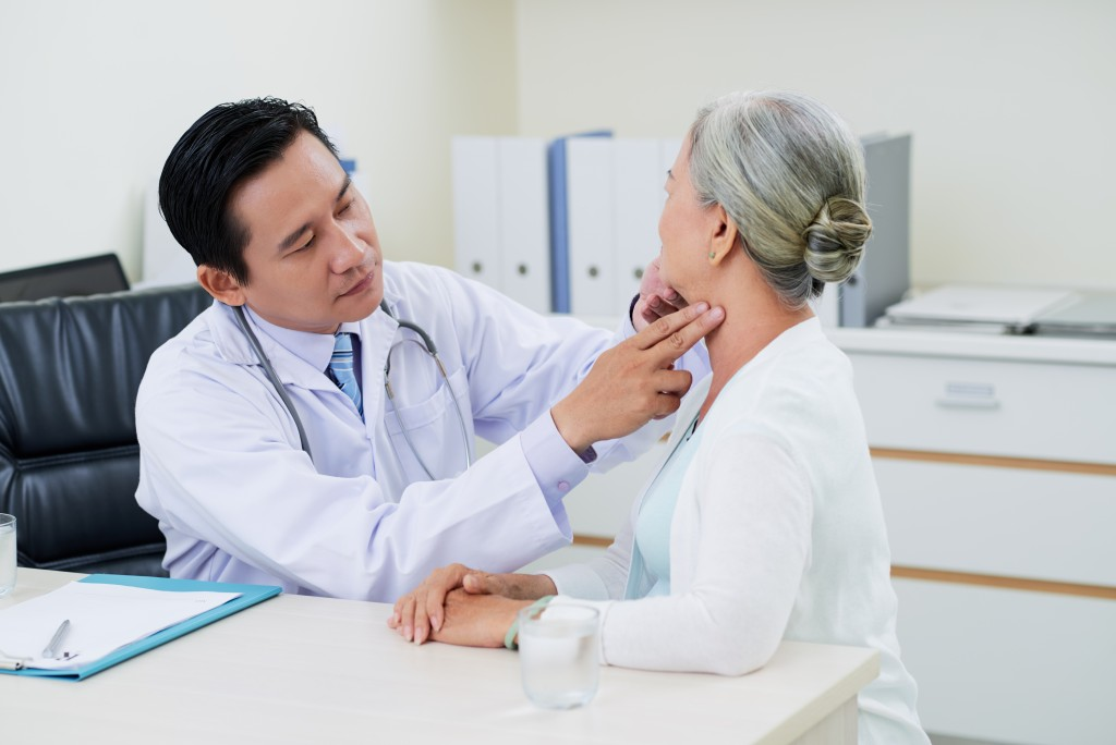 doctor examining old woman
