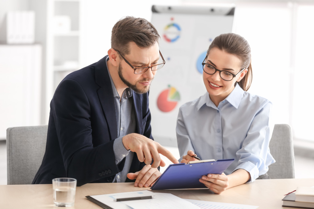 man and woman discussing with a clipboard
